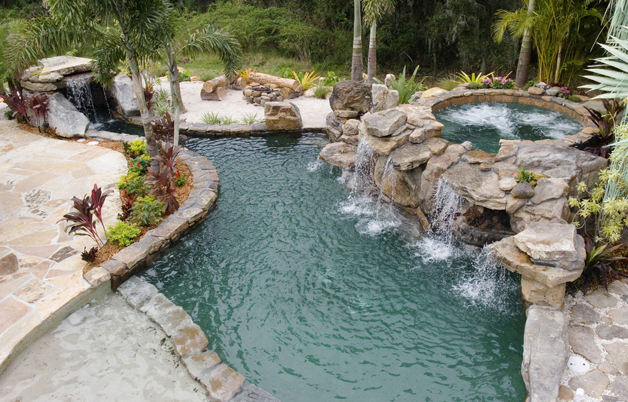 Natural stone grotto waterfall with elevated spa lucas for Natural rock swimming pools