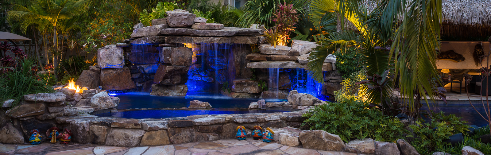 Custom Rock Waterfall Pool with Grotto, Spa, Natural Stream and Tiki Hut